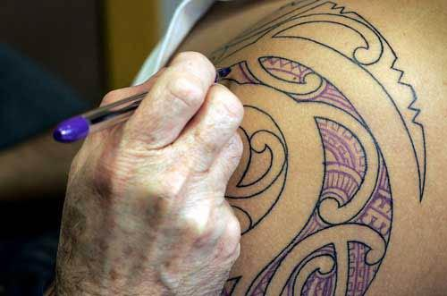 Inside the previously tattooed outline, Trevor Marshall pens in the design he will be tattooing.