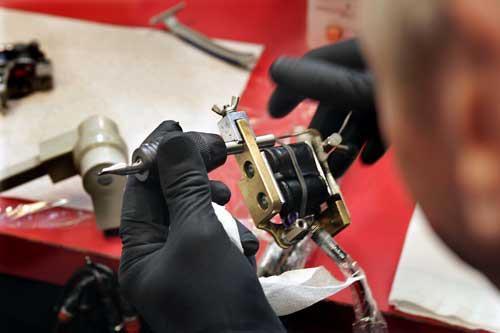 Trevor prepares his tattoo gun.