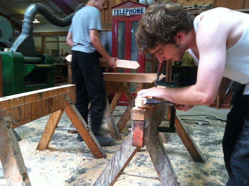 An apprentice compagnon works a timber with hand tools.