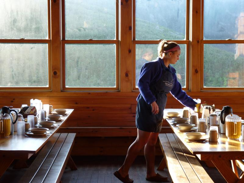 Emily Leich sets the table for breakfast at Greenleaf Hut.