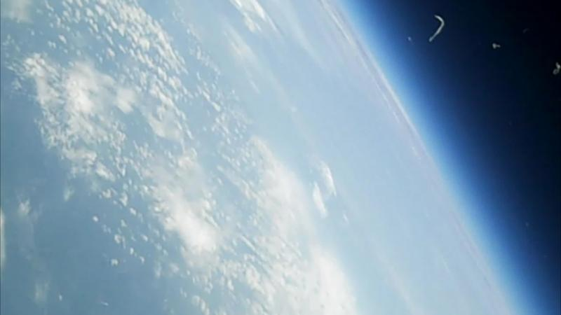 Earth from 105,900 feet, as seen by a camera on the Project SMART craft. The little marks in the photo are pieces of the just-burst weather balloon that lifted the craft into space.