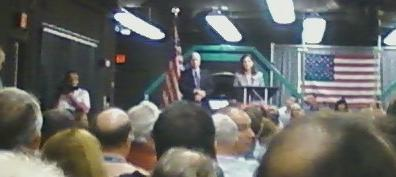 McCain and Ayotte speaking to a crowd inside a BAE building