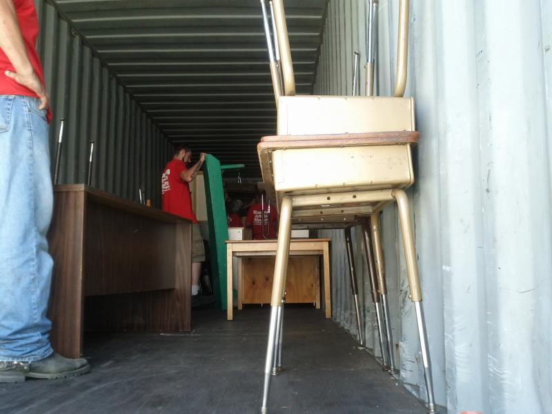 Shipping container half full of desks and chairs