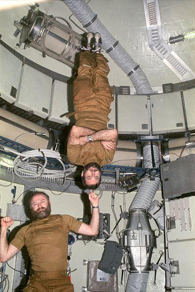 Carr demonstrates weightlessness by balancing Skylab 4 crewmate William R. Pogue on his finger.