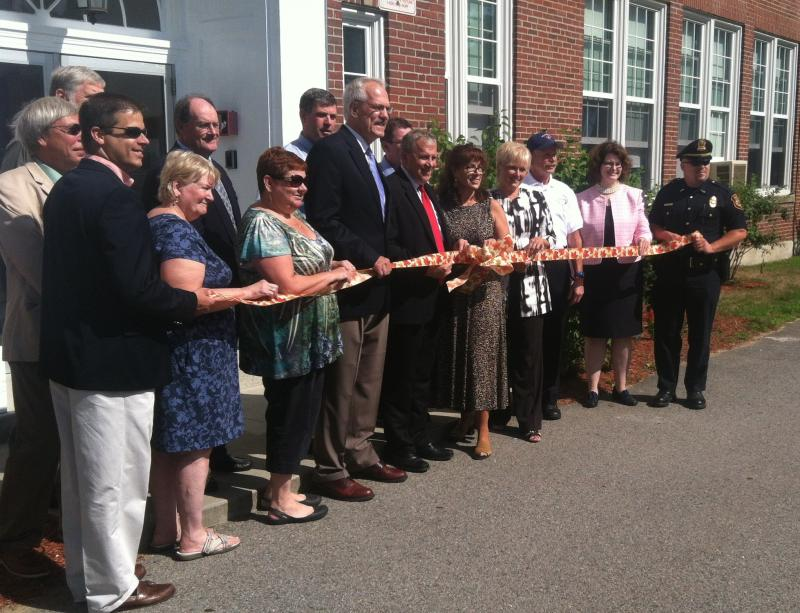 Rochester public figures pose for a ceremonial ribbon cutting at the Maple Street School