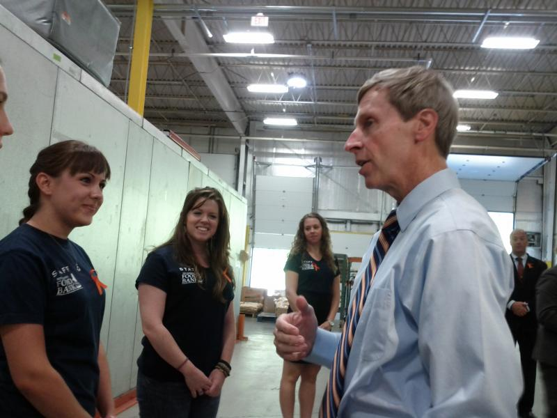 Lynch talks with Food Bank volunteers. They wore orange ribbons which symbolize hunger.
