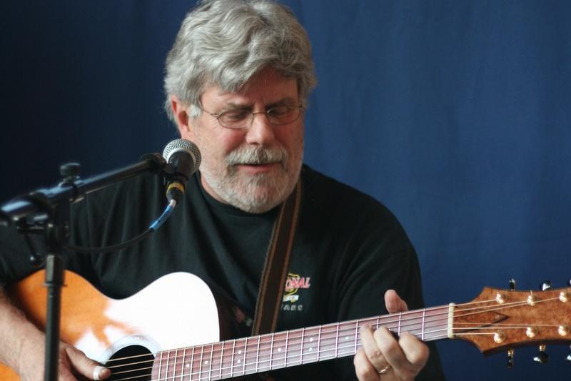 Folk Performer Bob McCarthy strums his guitar during a performance.