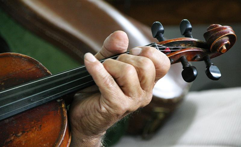 Jean Theroux leaned to play the fiddle working in logging camps more than 60 years ago.