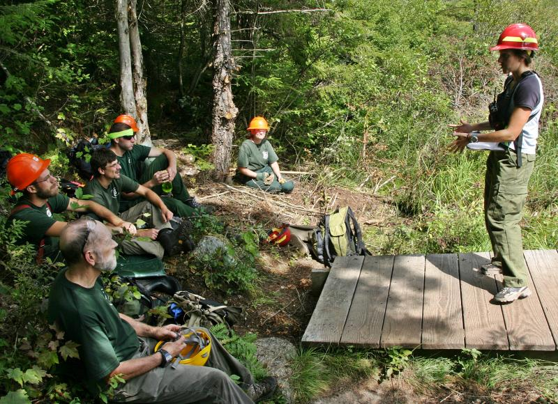 Giff Kriebel, far left, is among crew members listening to the Forest Service's Erin Lane brief them on helicopter deliveries.