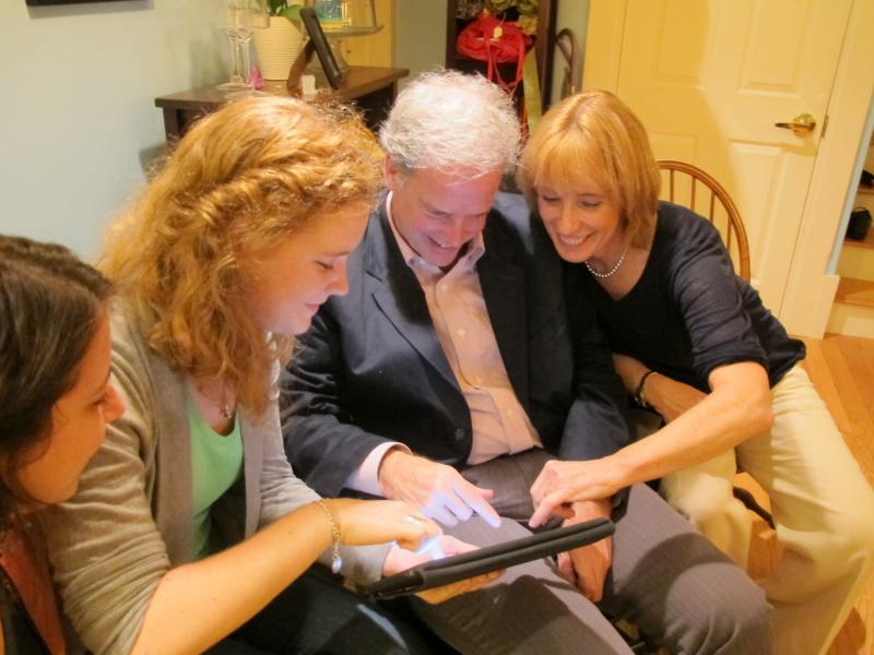 Maggie Hassan and her family laugh over pictures on an iPad