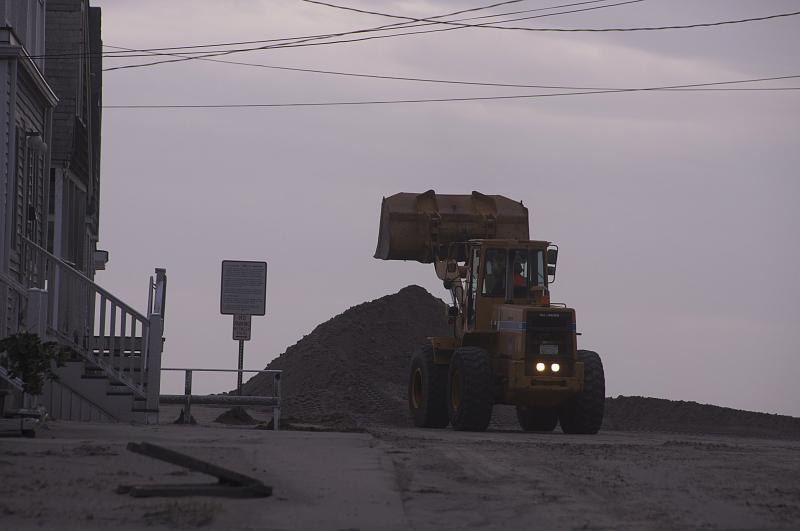 Hampton public works employees work to move sand that's drifted up onto streets
