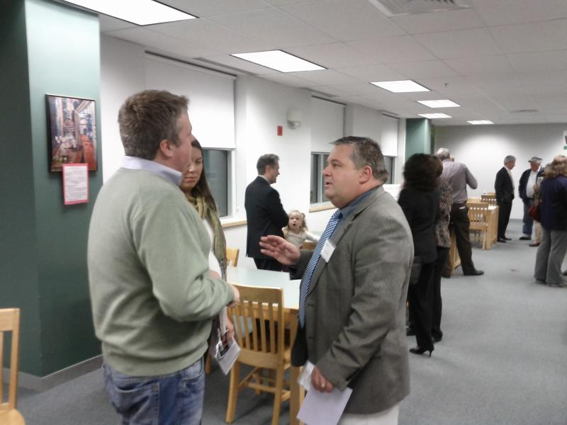 School board committee member Chris Stewart on left talking with CMS President Jim O'Connell on right.