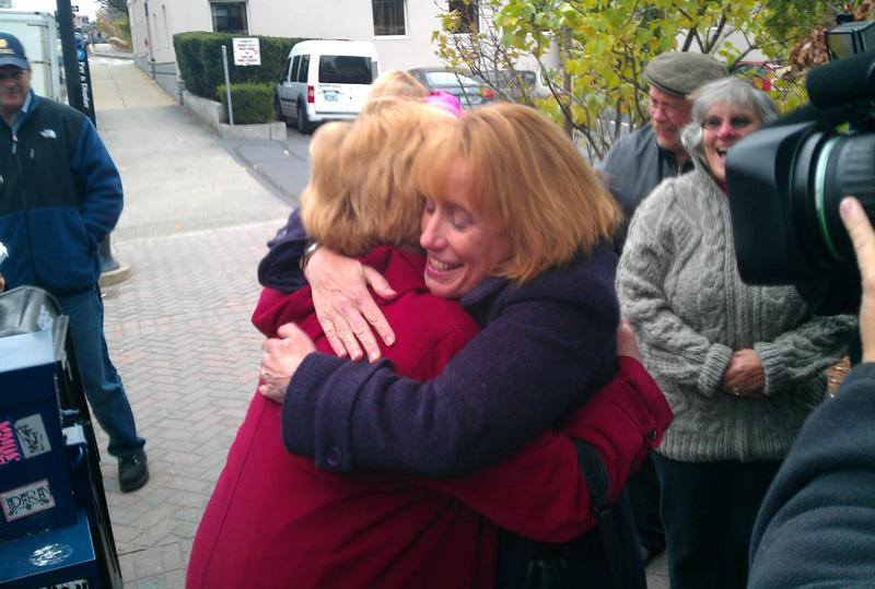 Hassan hugs a supporter outside of the Red Arrow in Manchester