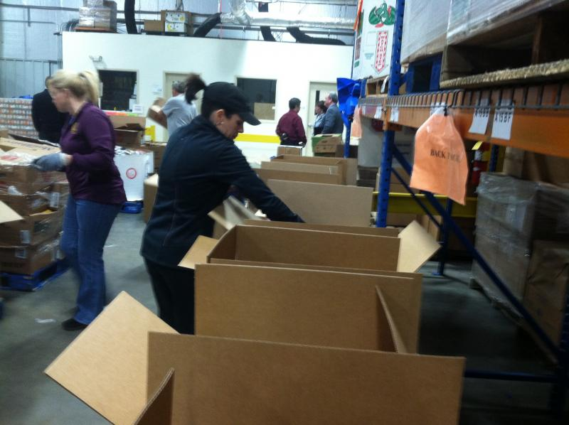 In the New Hampshire Food Bank warehouse, volunteers fill boxes with the donated goods.