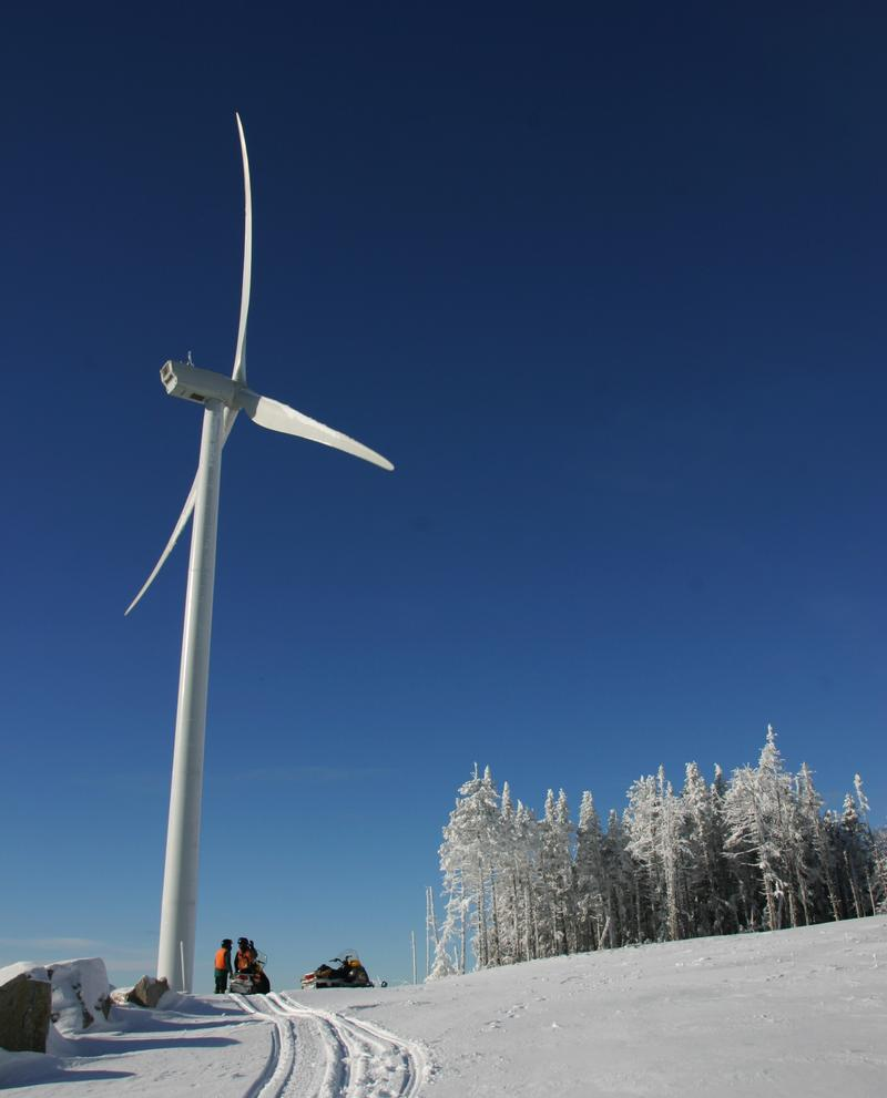 Researchers pause after reaching the top of Mount Kelsey where a wind turbine makes trees look like toys.