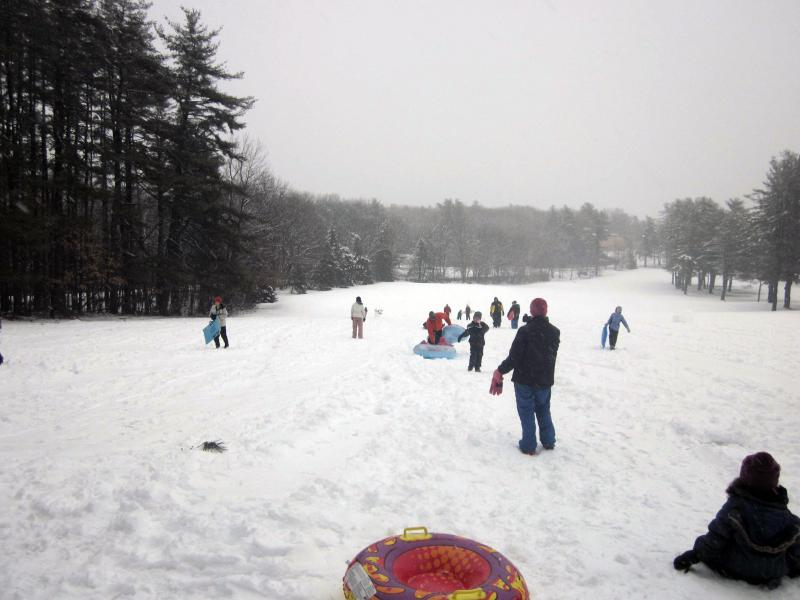 Families sled down a hill at Derryfield Country Club.