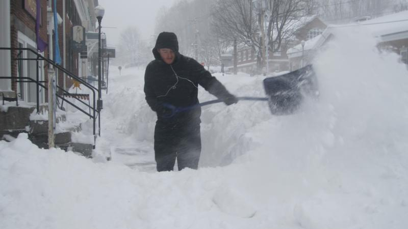 A man works to clear the sidewalk in downtown Peterborough.