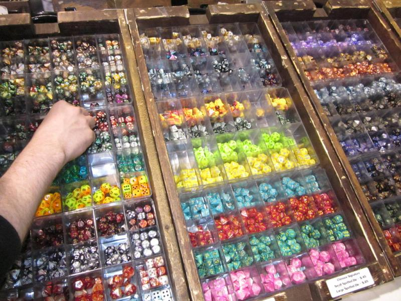 A gamer browses dice from a vendor's display