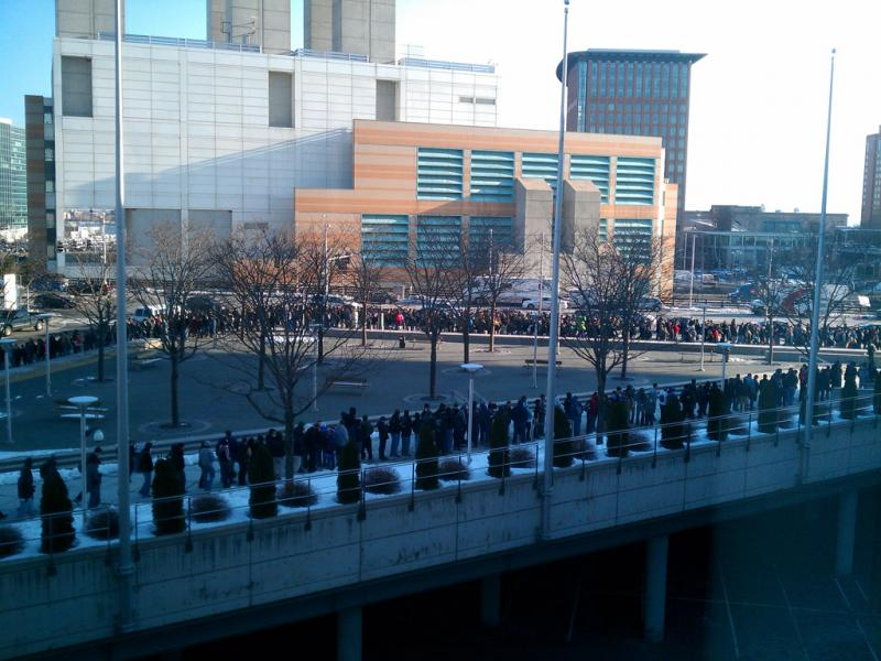 A line of attendees stretches around the front of the convention center