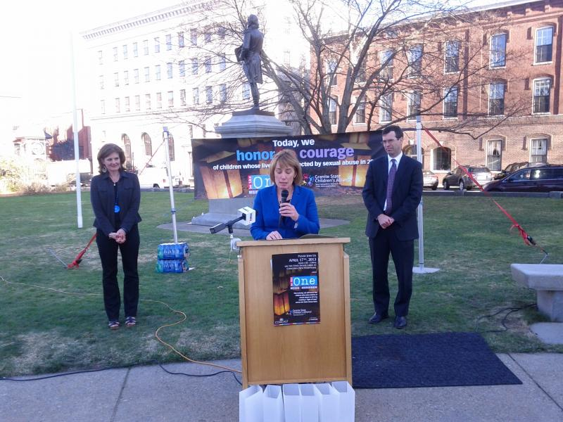 Kristie Palestino and Michael Delaney flank Governor Maggie Hassan as she reads from her proclamation.