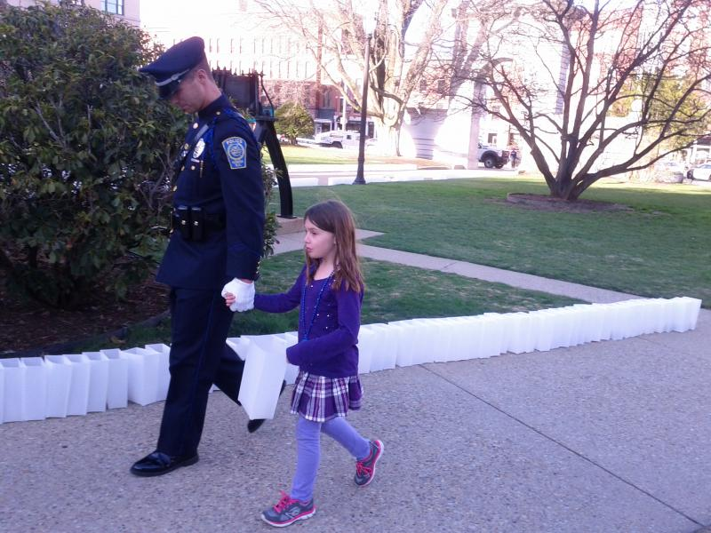 Nashua Detective in his dress blues walks girl down luminary-lined walkway towards the state house.