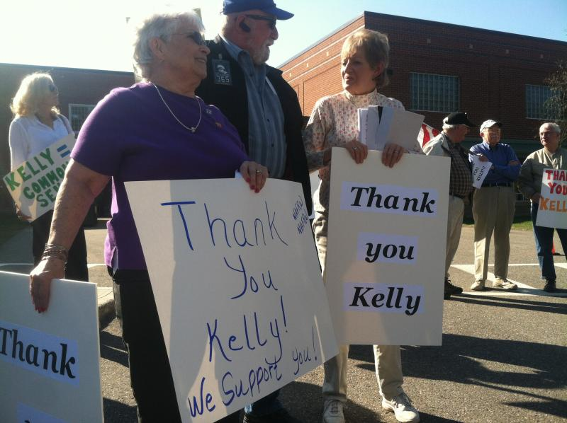 Linda Twombly, left, and Sarah Brown, right, hold signs supporting Sen. Kelly Ayotte before a town hall meeting in Tilton on Tuesday.