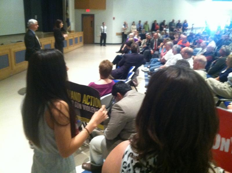 Despite a rule barring signs, two protesters were allowed to stay during Sen. Ayotte's town hall in Tilton on Tuesday.