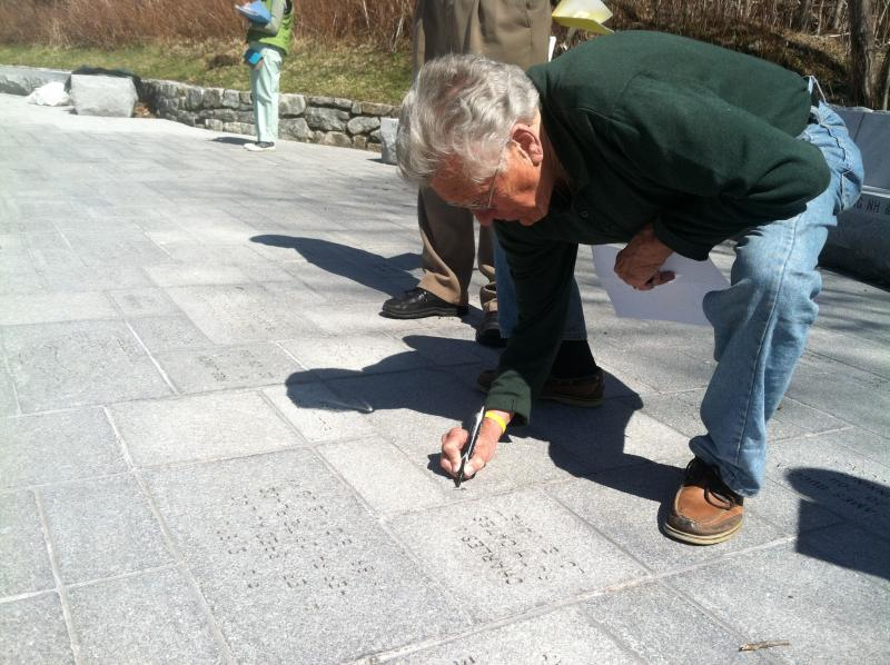 Dick Hamilton marks off stones at the Profile Plaza that have been reserved.