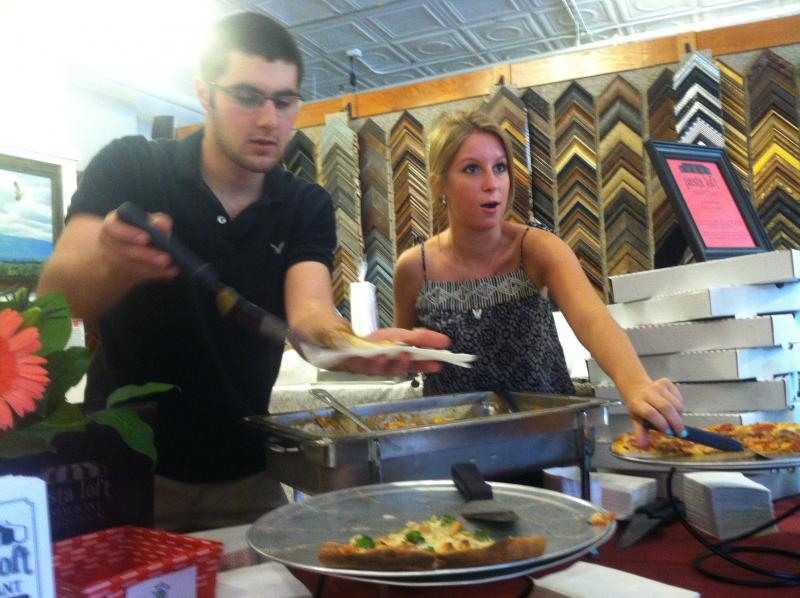 Zack Cronin and Molly Mendola from The Pasta Loft serve pizza and chicken spinach ravioli inside The Frame Depot.