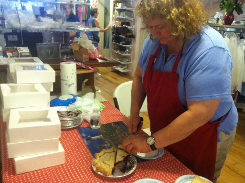 Karen Grybko of Maple Lane Farm cuts up slices of pie inside the I Do Again Bridal Boutique.