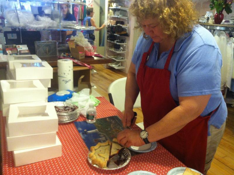 Karen Grybko of Maple Lane Farm cuts up slices of pie inside the I Do Again Bridal Boutique.