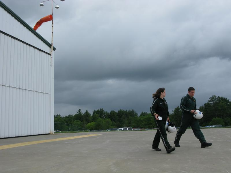Pilots walk out to the unit as a thunderstorm rolls in.
