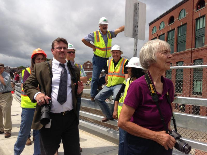 Construction crews and spectators try to get a view of 95 year old former Mayor Eileen Foley, as she cuts the Memorial Bridge ribbon.