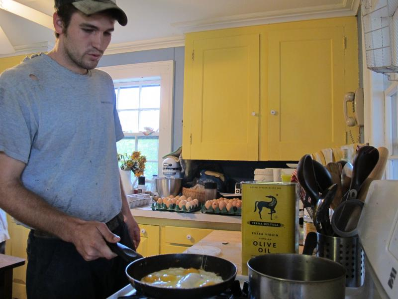 Brand cooks eggs from his farm's chickens before starting the day.