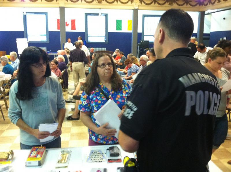 Officer Paul Rondeau shows people at the community meeting various options for home security.