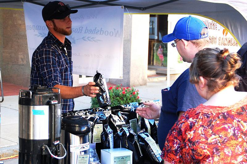 Kevin Grollo (left) of Woodshed Coffee Roasters shows off some of the local blend at the New Hampshire Coffee Festival in Laconia.