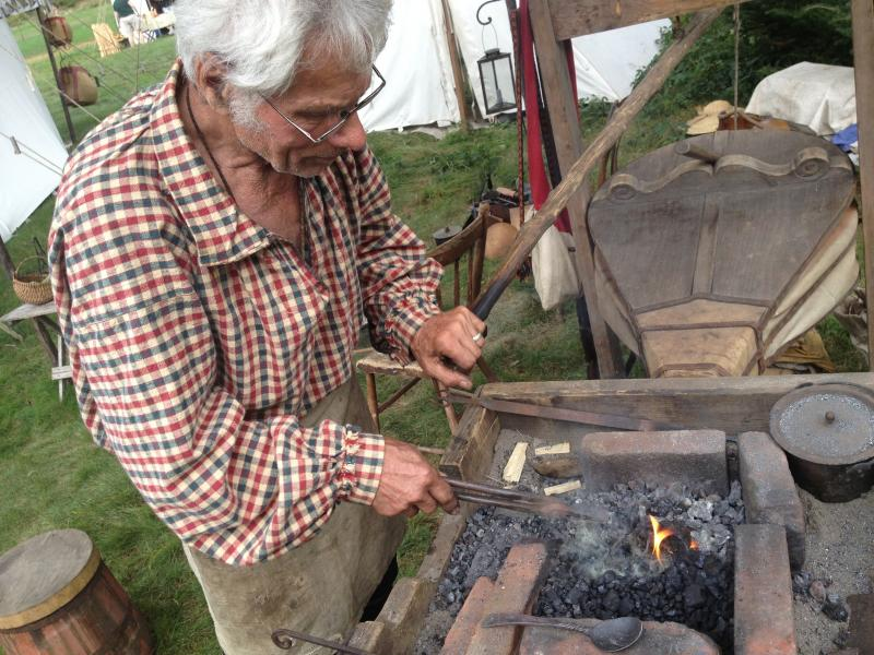 Blacksmith Bob Anderson turns a bar a metal into a spoon.