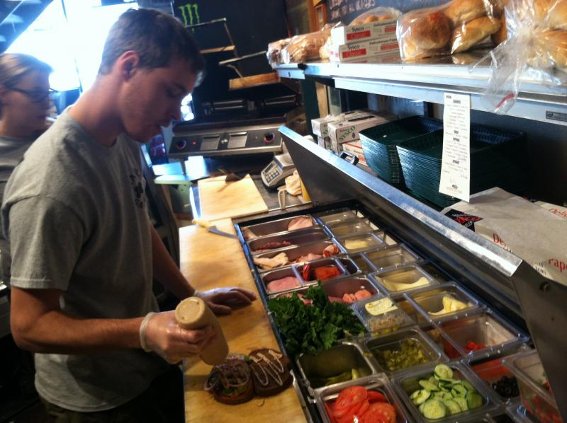 Manager Zach Dion prepares a sandwich at the Nashua Garden.