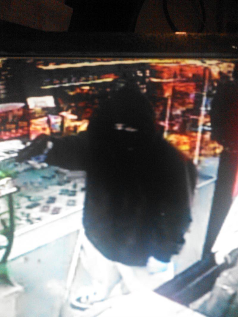 A robber points a gun at the clerk of a Manchester gas station this past September.