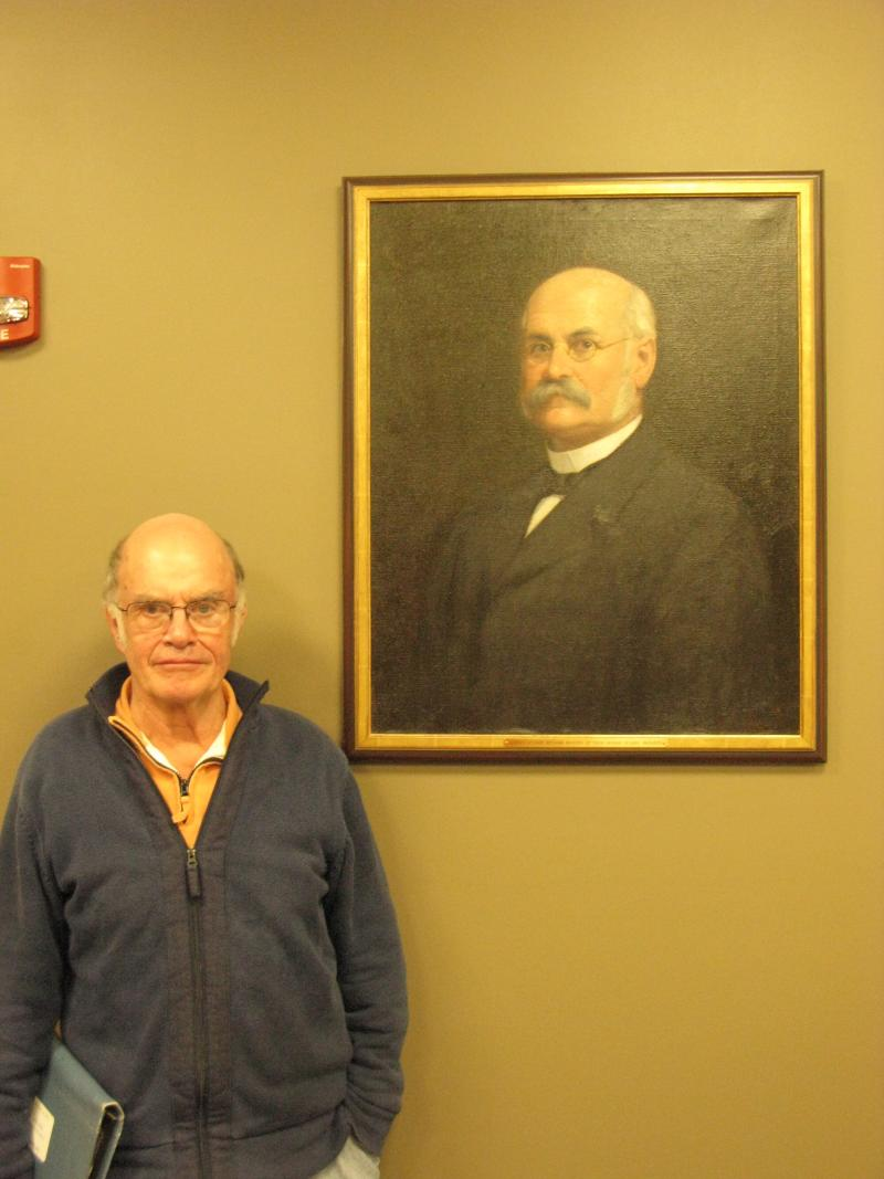 Sandwich Resident Lee Quimby standing next to a portrait of his Grandfather who was a major benefactor of town