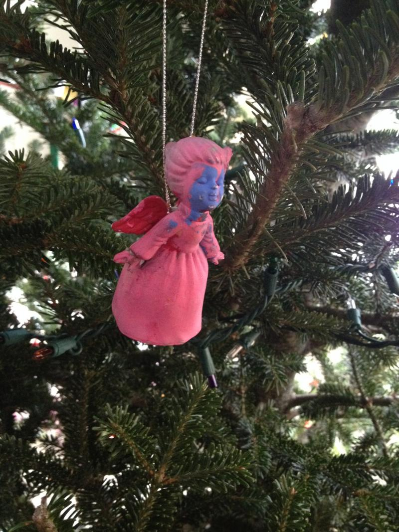 """I painted this when I was 4.  I was very into pink, but apparently felt that the face needed something more.  She looks like she was strangled.  My husband calls this the Christmas Angel of Death, & she goes front & center on the tree every year."""