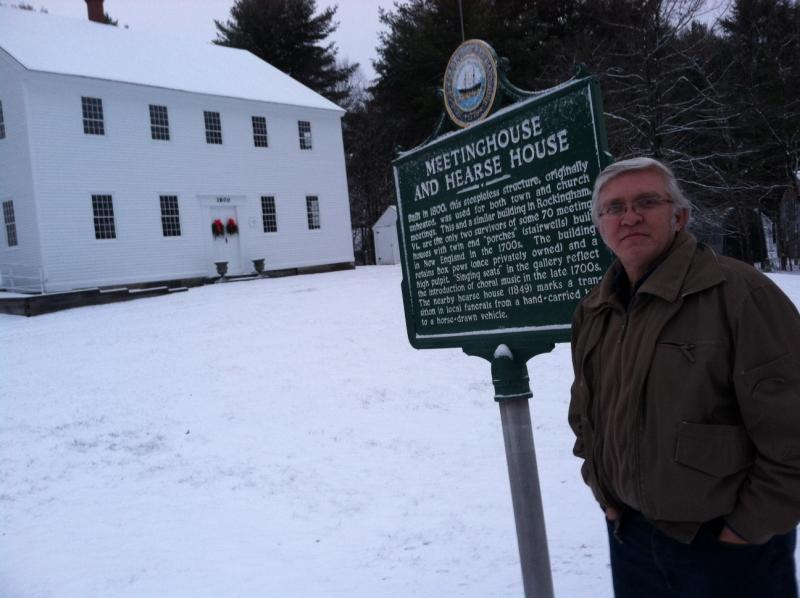 Town historian Matthew Thomas stands in front of the Meetinghouse in Fremont.