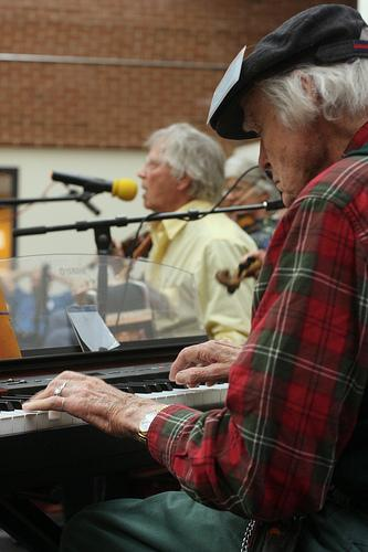 Bob McQuillen playing piano at a contra dance with Dudley Laufman calling