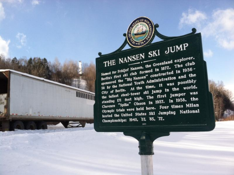 The state put up the historical marker for the Nansen Ski Jump in 2011. The top of the jump can be seen in the background.