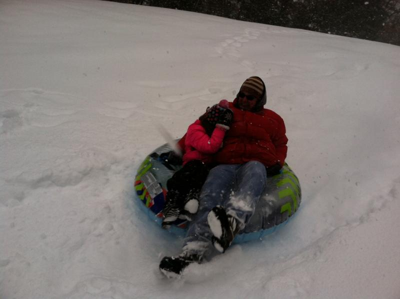 Cliff Favereau and his daughter Leah slide down a hill at Alexander Carr Park in Derry Wednesday.