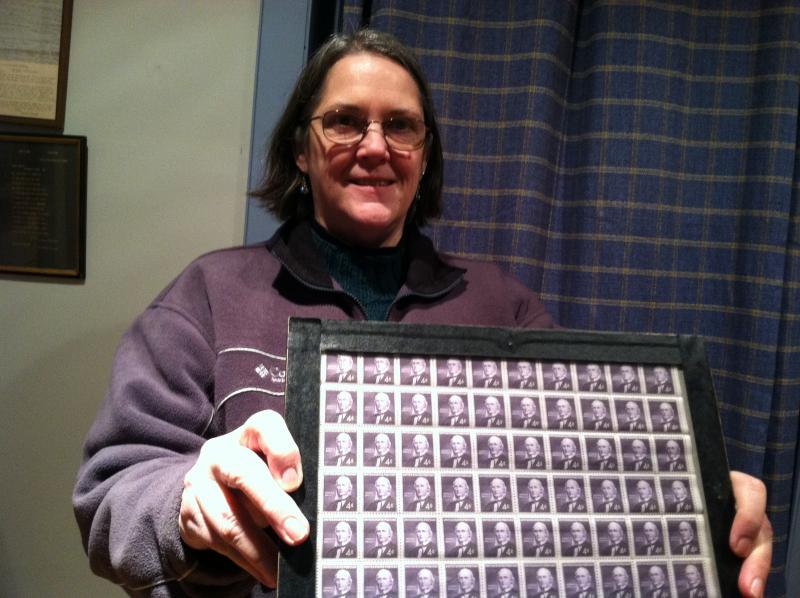 Jackie Marshall holds up a sheet of commemorative Horace Greeley stamps.