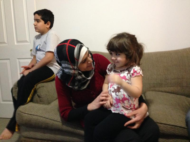 Nidhal Qaraghuli with some of her own kids in her Manchester apartment.
