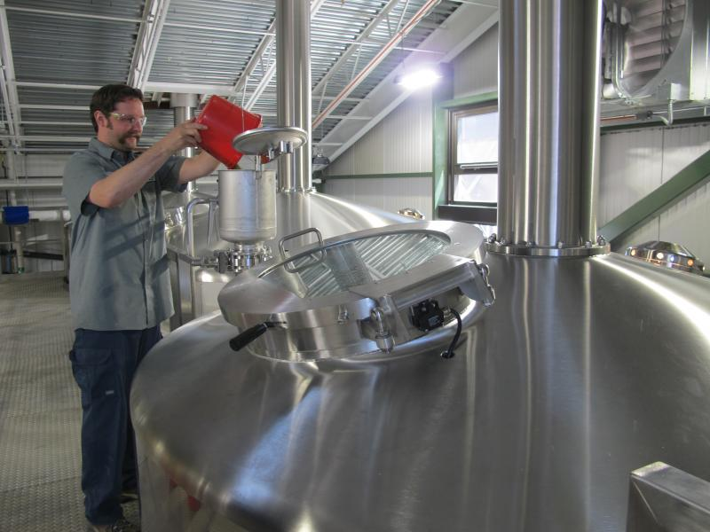 Lead brewer Dan Schubert adds hops to a kettle of boiling nonfermented beer, or wert.