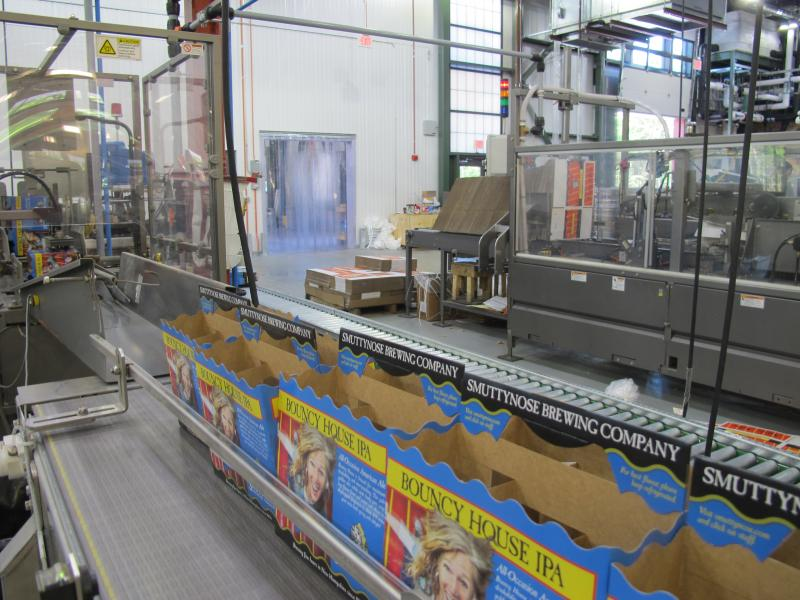 "Cardboard boxes for Smuttynose's ""Bouncy House IPA"" are mechnanically expanded and placed onto a conveyer belt."