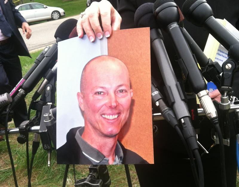 Assistant Attorney General Jane Young holds up a photo of officer Steve Arkell.